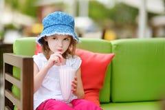 A girl drinking milkshake in outdoor restaurant Stock Image