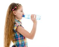 Girl drinking mineral water from bottle. Teen girl drinking mineral water from plastic bottle isolated on white background Royalty Free Stock Image