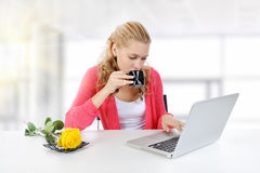 Girl drinking morning coffee in the office. Royalty Free Stock Photos