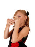 Girl drinking from a mug. Stock Images