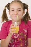 Girl drinking orange juice II. The nice girl-teenager drinking orange juice Royalty Free Stock Photos