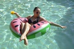 Girl drinking orange juice on watermellon float. Girl with sunglasses drinking the orange juice on the pool, relaxing in the watermellon float Stock Photos