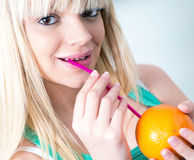 Girl drinking an orange from a straw Stock Images