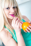 Girl drinking an orange from a straw Stock Photo