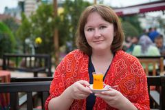 Girl drinking orange tea Royalty Free Stock Image