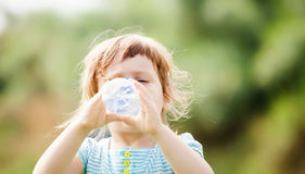 Girl drinking from plastic bottle Royalty Free Stock Image