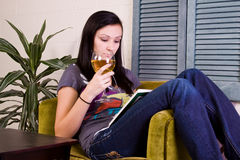 Girl Drinking while Reading a Book Stock Photography