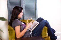 Girl Drinking while Reading a Book Royalty Free Stock Photos