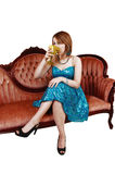 Girl drinking on sofa. Stock Image