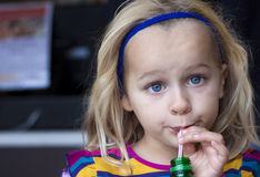 Girl drinking with straw. A young child drinking from a bottle with a straw. Humor, funny face, candid shot royalty free stock image