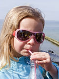 Girl drinking with a straw. Seaside portrait of a cute little girl wearing pink  sunglasses, drinking from a plastic bottle with a straw Stock Image