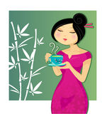 Girl drinking tea. Asian girl drinking a cup of green tea Royalty Free Stock Photo