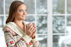 Girl drinking tea. Beautiful girl in warm sweater drinking tea near the window Stock Photography