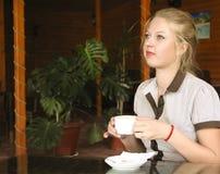 A girl drinking tea. In a cafe stock photos