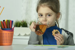 Girl  drinking tea and eating cookie Stock Image
