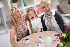 Girl drinking tea with her mom and grandmother. Laughing girl drinking tea with her mom and grandmother Royalty Free Stock Photos