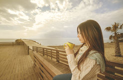 Girl drinking a tea in a mug warm filter applied Stock Photo