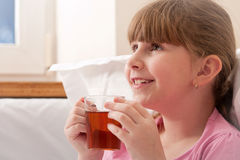 Girl drinking tea while sitting in bed. Close-up. Stock Image