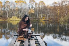 Girl drinking tea on a wooden bridge on a lake. Young beautiful girl drinking tea on a wooden old bridge on a lake in the picturesque autumn forest. Toning Stock Image