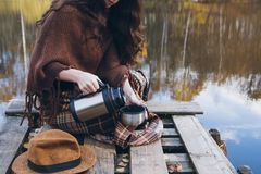 Girl drinking tea on a wooden bridge on a lake. Young beautiful girl drinking tea on a wooden old bridge on a lake in the picturesque autumn forest. Toning Royalty Free Stock Photos