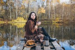 Girl drinking tea on a wooden bridge on a lake. Young beautiful girl drinking tea on a wooden old bridge on a lake in the picturesque autumn forest. Toning Stock Photos