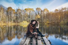Girl drinking tea on a wooden bridge on a lake. Young beautiful girl drinking tea on a wooden old bridge on a lake in the picturesque autumn forest. Toning Stock Photo