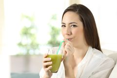 Girl drinking a vegetable green juice looking at you Royalty Free Stock Photos