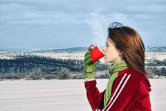 Girl drinking warm beverage Royalty Free Stock Images