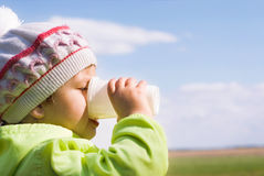 Girl drinking water. Against the sky Royalty Free Stock Photos