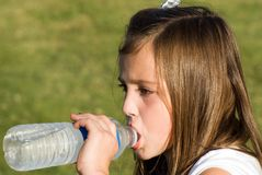 Girl Drinking Water. Young girl who was thirsty after playing in the sun royalty free stock photography