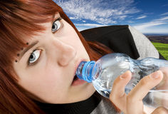 Girl drinking water. Seductive redhead girl looking at camera and drinking a bottle of water. Studio shot royalty free stock image