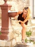 Girl drinking water. Girl in black miniskirt is preparing to drink water Royalty Free Stock Images