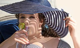Girl drinking water. Gorgeous teen girl drinking water on the beach Royalty Free Stock Photography
