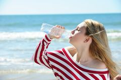 Girl drinking water on the beach. Woman drinking water on the beach royalty free stock photography