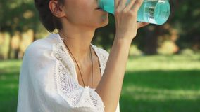 Girl is drinking water between diong yoga