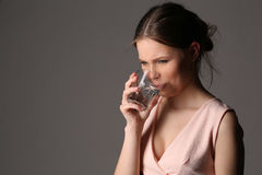 Girl drinking water is dissatisfied. Close up. Gray background Stock Photo