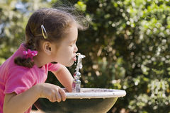 Girl drinking from water fountain. Young girl drinking from park water fountain.  Out of focus foliage background.  Water motion frozen Royalty Free Stock Images
