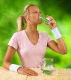 A girl drinking water from glass. On a background of green bokeh royalty free stock image