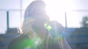 Girl drinking water from a glass bottle in the beautiful sunlight. Very beautiful lighting. Cinematic slow motion. Girl sitting on the podium of the school stock footage