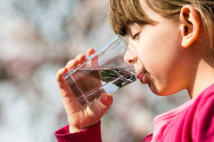 Girl drinking water from glass stock images