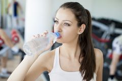 Girl drinking water in the gym Stock Image