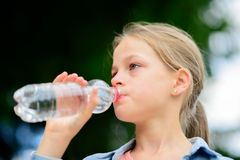Girl drinking water outdoors Stock Photography