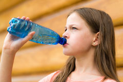 Girl drinking water outdoors Stock Images
