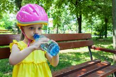 Girl drinking water in the park while resting on a bench Royalty Free Stock Photos