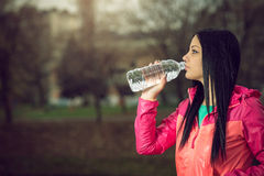 Girl drinking water in park. Young adult girl drinking water from bottle in park Stock Photo
