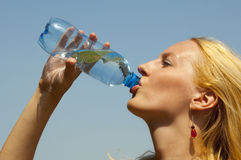 Girl drinking water from a plastic bottle Royalty Free Stock Photo