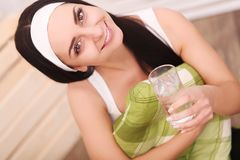Girl drinking water sitting on a couch at home and looking at ca Stock Photography