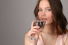Girl drinking water from a wine glass. Close up. Gray background royalty free stock image