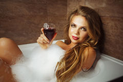 Girl is drinking wine in bath with foam. Royalty Free Stock Images