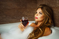Girl is drinking wine in bath with foam. Stock Image